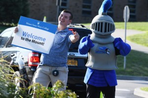 "Student stands next to Mack the Knight (mascot) holding sign that reads ""Welcome to the Mount!"""