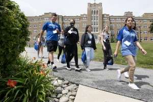 Group of students walk across campus with building behind them