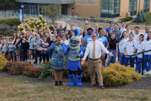 Group of MSMC students and mascot Mack the Knight stand on greenery hill, welcoming students.