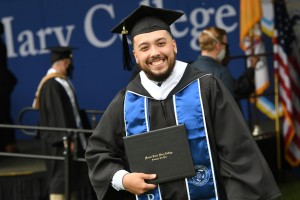 Graduating student in cap and gown holding up his diploma