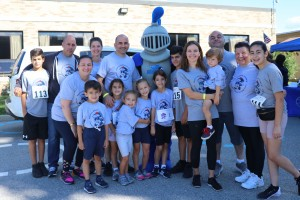 A group of adult and children volunteers and participants standing with the Mount's mascot, Mack the Knight, at the Cupcake 5K Run/Walk.