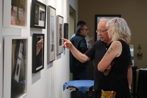 Two people discussing a photo displayed at the CMA gallery.
