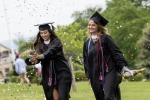 Two Mount graduates pop champagne in their caps and gowns.