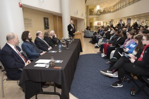 Michael L. Fox addressing the panel at a similar 2018 School of Business panel with a crowd seated in front of him.