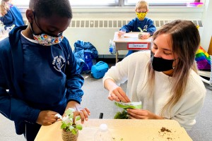 Student teacher Elizabeth Cambronero photographed with a student making a terrarium.