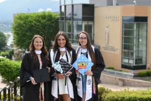 From left to right: Olivia Pelliccia, Nicole Cervone, and Renee Hydo standing holding their caps at the Mount's 2021 Commencement ceremony.