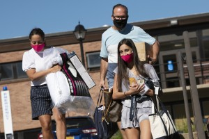 Family moves student into residence hall on move in day, wearing masks