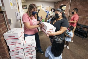 Rebecca Norman distributing free book boxes to Newburgh Armory Unity Center students after the Saturday morning literacy program.