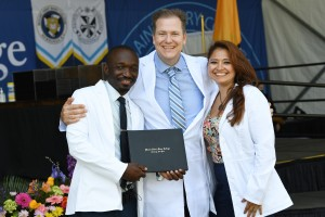 Three nursing graduates standing together at Commencement in May 2021.