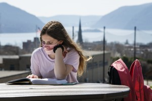 """Mount Saint Mary College education major Lauren Obergh studies at one of the tables at the south end of the Dominican Center with the Hudson River and Stormking in the background on April 6, 2021."""