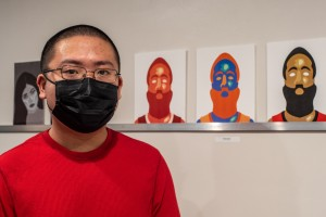 Mount student Michael Zhang at the exhibit with student art displayed in the background.