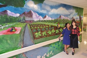 Mount professor stands with daughter in front of hand painted mural