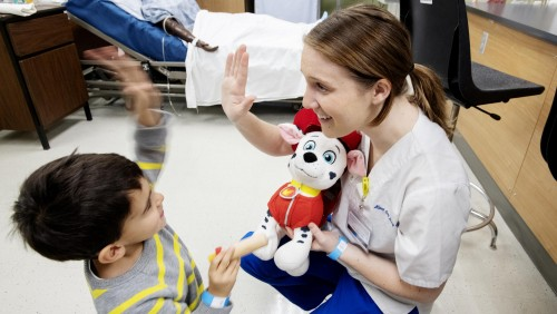 Nurse giving a young boy a high five while holding a stuffed animal