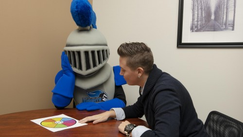 Director of Violence Prevention, Ashley Betta, sits with MSMC mascot Mack the Knight.