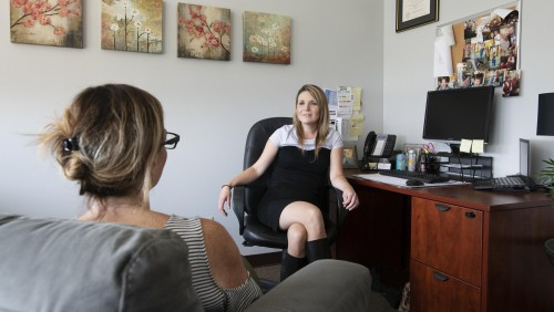 Female counselor speaks to students in office.