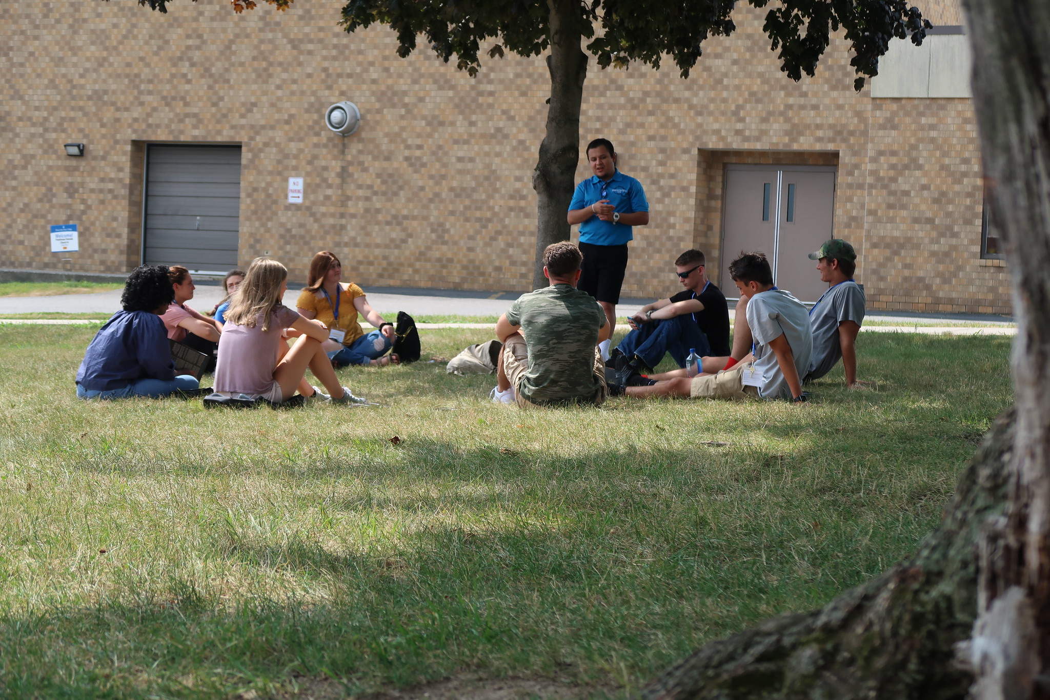 Students sitting in circle listening to Orientation Leader