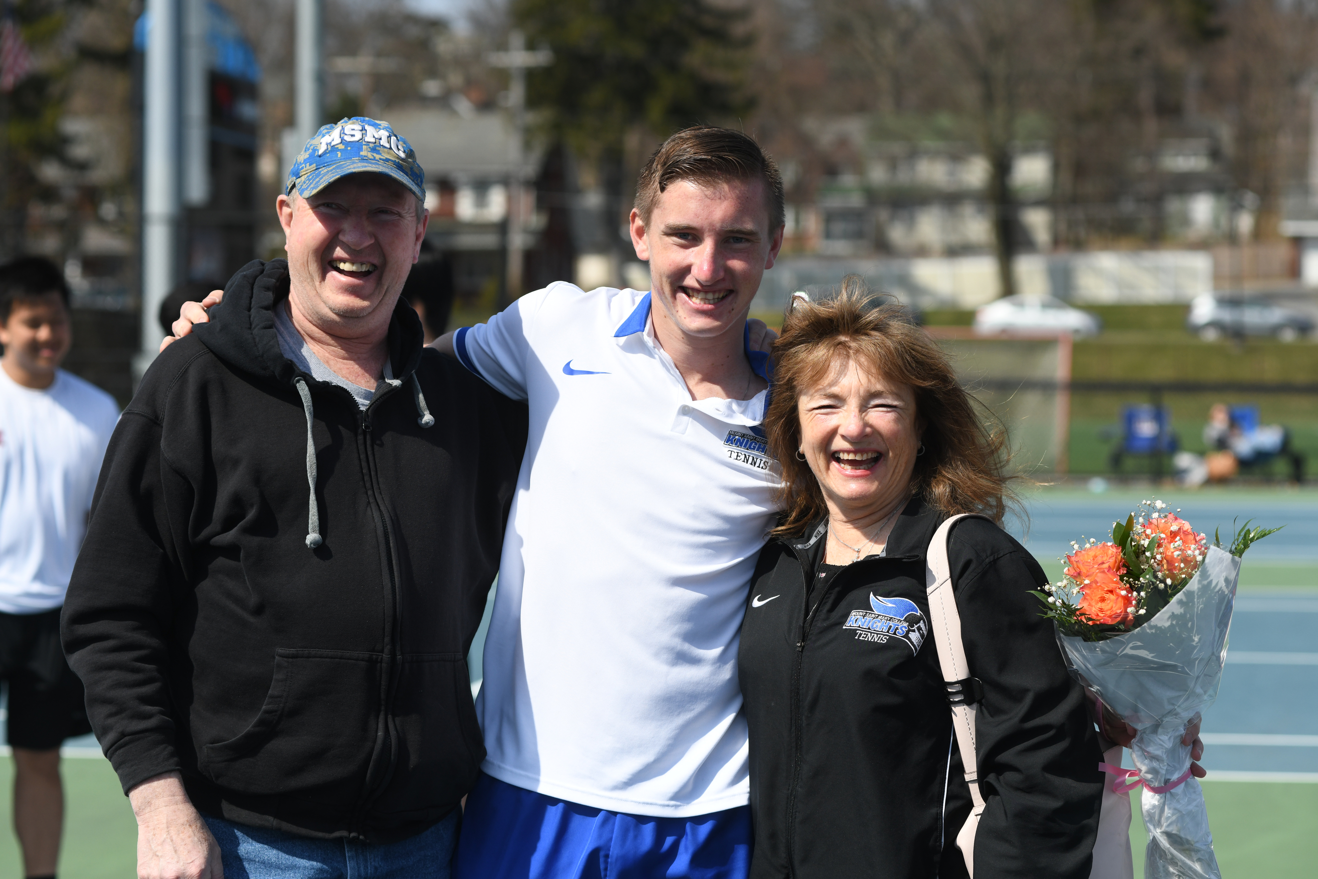Student with parents on tennis courts