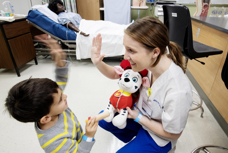 Nurse high fiving a kid