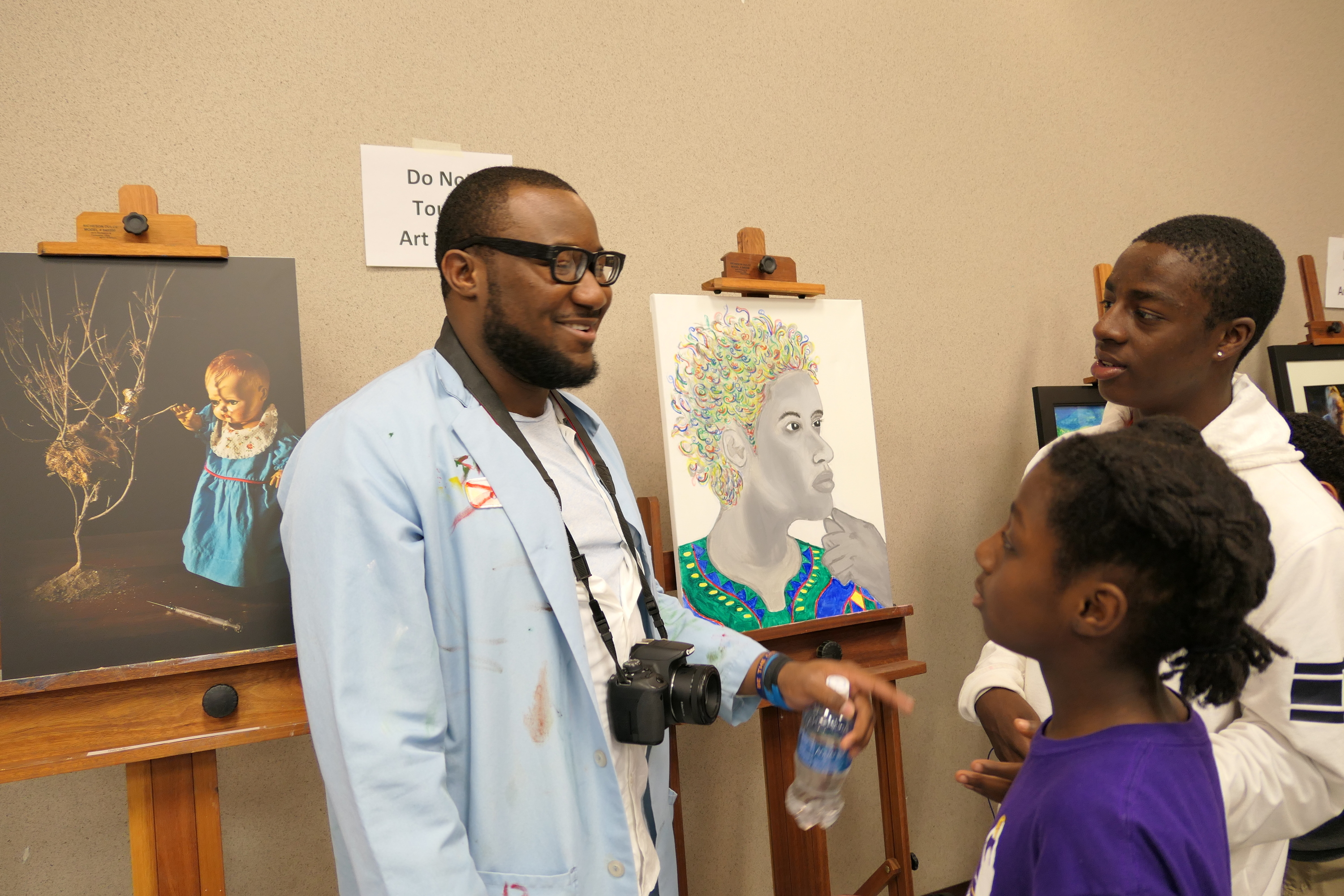 Student with a camera showing off artwork
