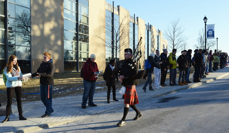 Brett Bondar, Information Technology Support Center coordinator, leads the first book down the human chain with traditional bagpipe music