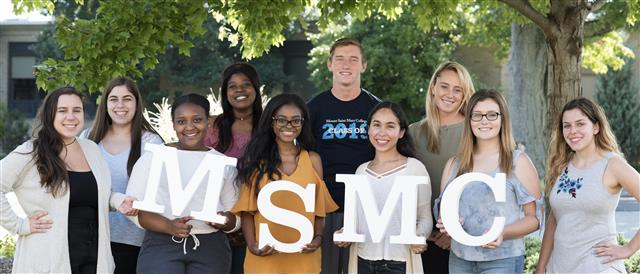Group photo with students holding MSMC letters