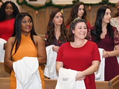 Nurses standing in church aisles holding their white coat.