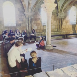 Teacher teaching in stone building with students in circle