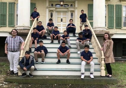 Students sit outside old house