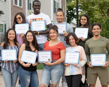 Students holding certificates of achievement