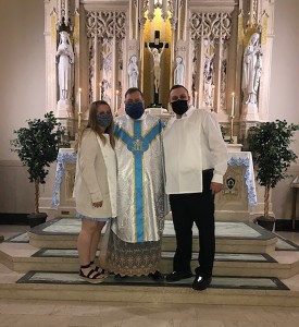 Sarah Carson, Father Gregoire Fluet, and Joshua Carson standing at the church alter.