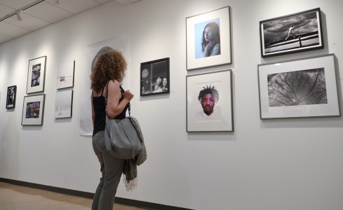 A woman looking at photography at the CMA gallery.