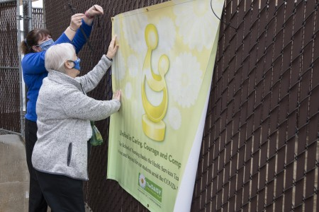 Doreen Bischof and Susan LaRocco hang the DAISY Dedication banner outside of the Health Services office