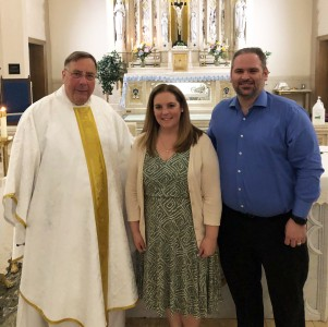 Fr. Gregoire Fluet, Kayla Gori, and Gori's husband Lido Gori standing together in front of the church alter.