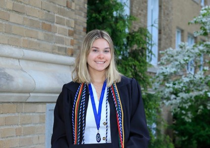 Jessica Musacchio standing outside in her graduation gown.