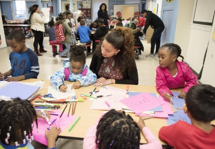 Students working with younger children volunteering on crafts