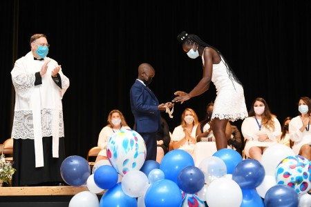 Nursing graduate receives pin on stage by her son.
