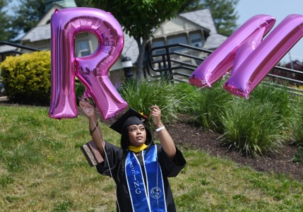 """A Mount Nursing graduate in her cap and gown holding an """"R"""" and """"N"""" balloons."""