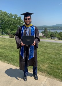 Sean Leuschner photographed in his cap and gown holding his diploma.